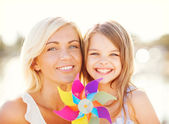 Happy mother and child girl with pinwheel toy — Stock Photo