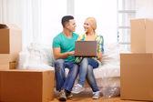 Iki yeni ev içinde laptop ile kanepede rahatlatıcı — Stok fotoğraf