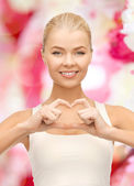 Smiling young woman showing heart shape gesture — Stock fotografie