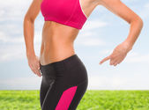 Close up of sporty woman pointing at her buttocks — Stok fotoğraf