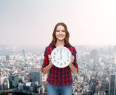 Young woman in casual clothes with wall clock — Stock Photo