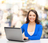 Smiling woman in blue clothes with laptop computer — Stock fotografie