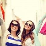 lächelnd mädchen Sonnenbrillen mit Einkaufstüten — Stockfoto #45673829