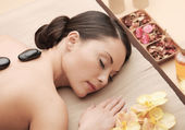 Asian woman in spa with hot stones — Stock fotografie