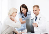 Doctors with patient looking at x-ray — Stock Photo
