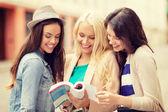 Belle ragazze in cerca nel libro turistico in città — Foto Stock