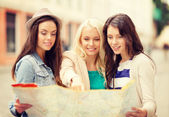 Belas garotas olhando no mapa turístico na cidade — Fotografia Stock