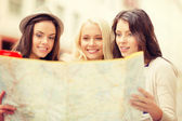 Beautiful girls looking into tourist map in city — Φωτογραφία Αρχείου