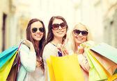 Três meninas sorridentes com sacos de compras na cidade — Fotografia Stock