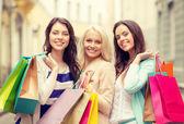 三个女孩微笑与城购物袋 — 图库照片