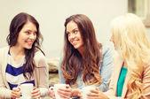 Three beautiful girls drinking coffee in cafe — Foto Stock