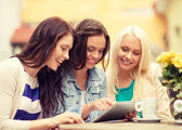Three beautiful girls looking at tablet pc in cafe — Photo