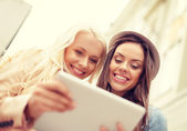 Two beautiful girls looking into tablet pc — Stock Photo