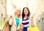 Belas mulheres com sacolas de compras no grosso — Fotografia Stock