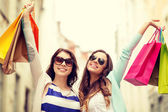 Smiling girls in sunglasses with shopping bags — Stock Photo