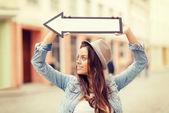 Ragazza mostrando la direzione con la freccia nella città — Foto Stock