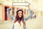 Girl showing direction with arrow in the city — Stock Photo