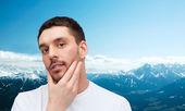 Bella uomo calmo, toccando il suo viso — Foto Stock