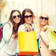 Three smiling girls with shopping bags in ctiy — Stockfoto