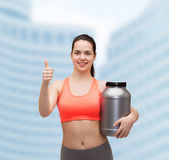 Teenage girl with jar of protein showing thumbs up — Foto de Stock