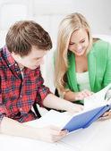 Uśmiechający się studentów, czytanie książki w szkole — Zdjęcie stockowe