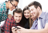 Students looking at smartphone — ストック写真