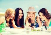 看着智能手机,在咖啡馆在海滩上的女孩 — 图库照片