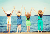 Girls looking at the sea with hands up — Stock Photo