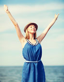 Girl with hands up on the beach — Stock Photo