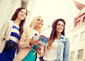 Three beautiful girls with tourist book in city — ストック写真