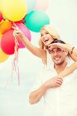 Paar mit bunten luftballons am meer — Stockfoto