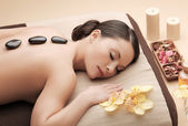 Asian woman in spa with hot stones — ストック写真