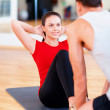 Male trainer with woman doing sit ups in the gym — Stock Photo
