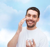 Beautiful smiling man applyin cream — Stock Photo