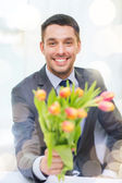 Smiling handsome man giving bouquet of flowers — Stock Photo