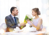 Smiling man giving flower bouquet at restaurant — Stockfoto