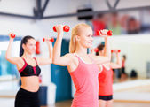 Group of smiling women working out with dumbbells — Stock Photo