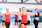 Group of smiling people exercising in the gym — Stock Photo