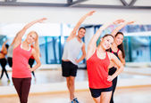 Group of smiling people stretching in the gym — Стоковое фото