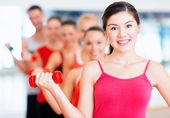 Group of smiling people with dumbbells in the gym — ストック写真