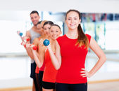 Group of smiling people with dumbbells in the gym — Stockfoto
