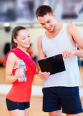Smiling male trainer with woman in the gym — Stock Photo