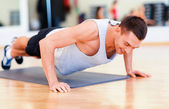 Smiling man doing push-ups in the gym — Stock Photo