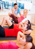 Group of smiling women doing sit ups in the gym — ストック写真