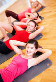 Group of smiling women exercising in the gym — Stock Photo