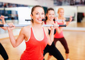 Group of smiling people working out with barbells — Stockfoto
