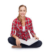 Smiling young woman sitting on floor with book — Stockfoto