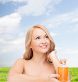 Happy woman with oil bottle — Stock Photo