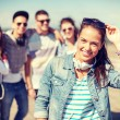 Teenage girl with headphones and friends outside — Stock Photo #46084307