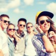 Teenage girl with headphones and friends outside — Foto de Stock